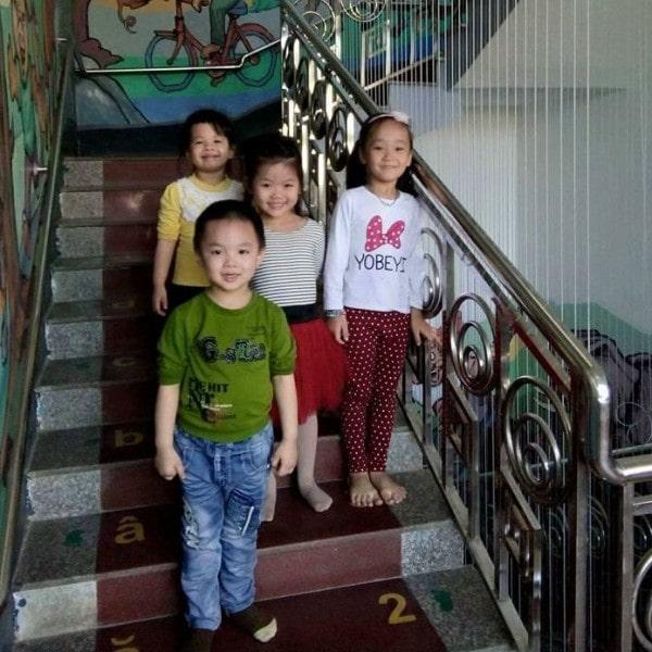 bé bên cạnh lưới cầu thang tại trường học